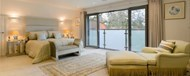 A large bedroom looking out through open doors onto a Juliet balcony