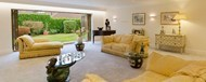 A large lounge with fully open bifold doors looking into the garden