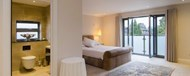 A double room with ensuite, rug and doors opening out onto a Juliet balcony