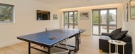 A games room with a table-tennis table, large wall-mounted TV, a leather sofa and two sets of folding doors