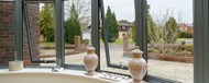 A close up of partially opened bay windows looking out onto the forecourt