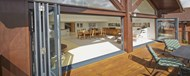 Looking into a modern stylish riverside property with the bifold doors fully opened