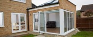 Looking into a garden room with large skylight through a partially opened folding door