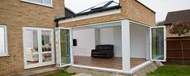 Looking into a garden room through fully opened folding doors that make up two walls of the room