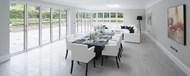 A bright dining area with large bifold doors and a corner door covering the length of the room