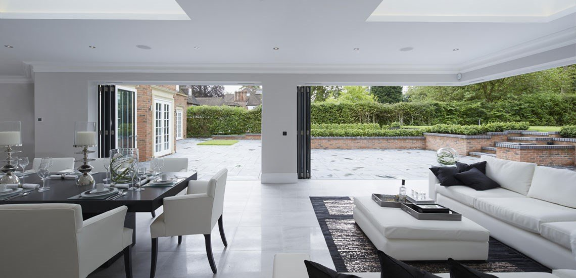 Looking out from a bright dining area through open folding doors into a paved area with raised lawn