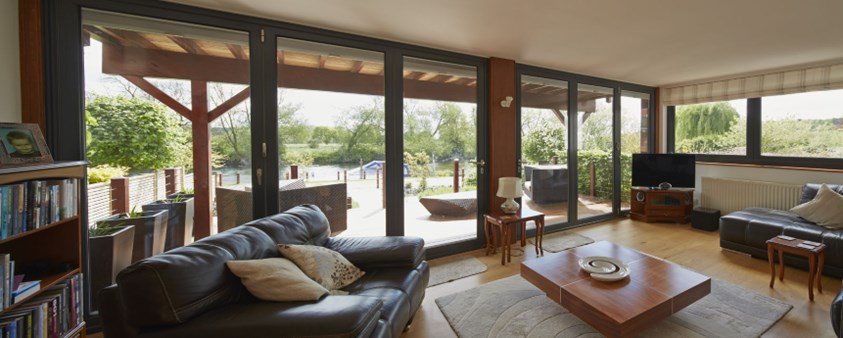 A view from the lounge, out through large bifold glass doors and over the river