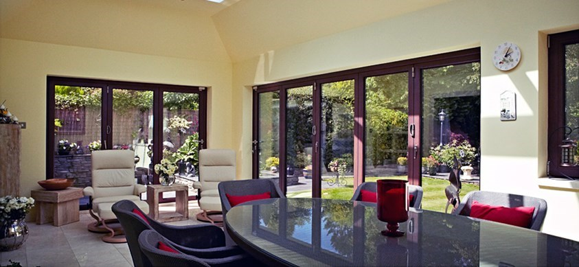 A bright house extension with a large table, comfortable chairs and large folding doors out to the garden
