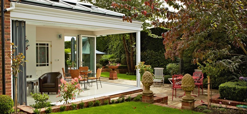 The view from the garden of a beautiful garden room, with folding doors fully opened up