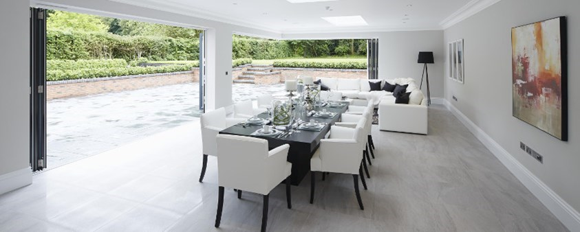 A bright dining area looking with a large folding door and corner door section fully open looking out onto a paved area