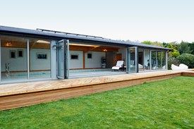 View of a pool house with open bifolding doors from a garden