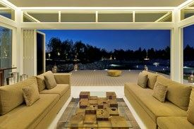 Modern living room opened onto patio area with lake side view at night
